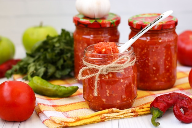 Homemade adzhika with tomatoes and apples in jars on white