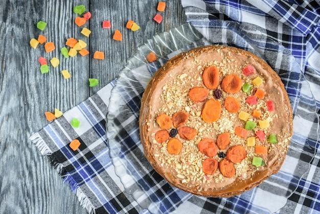 Домашний воздушный ореховый торт с шоколадным кремом, вареной сгущенкой, цукатами, орехами и курагой на сером деревянном пространстве.