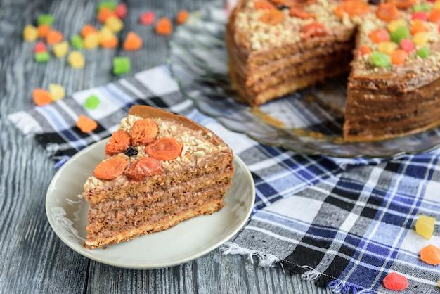 회색 나무 공간에 초콜릿 크림, 삶은 연유, 설탕에 절인 과일, 견과류 및 말린 살구로 만든 수제 에어 너트 케이크.