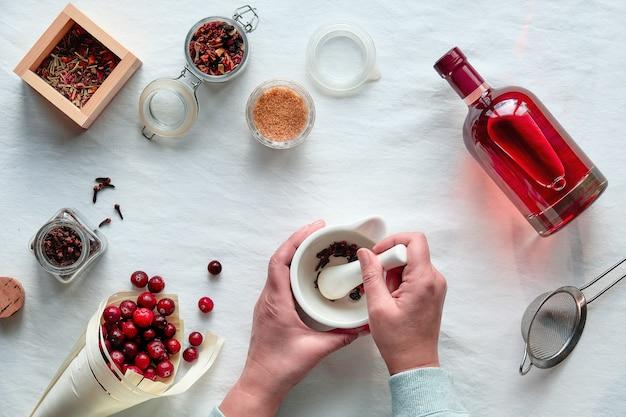 수제 알코올 음료 준비. 에탄올, 딸기 및 향신료가 들어간 크랜베리 팅크 위에 평평합니다.