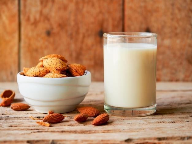 ビーガンフードのコンセプト、無料の乳糖食品のための自家製アーモンドミルクと生アーモンドボウル。