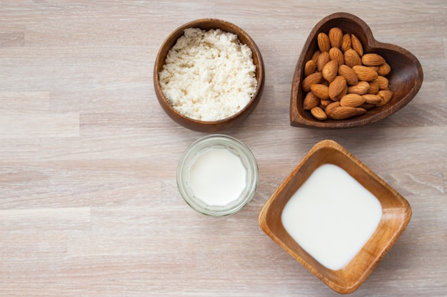 Homemade almond squeezed nut milk preparation on wooden background top above view