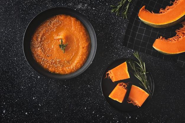 暗いテーブルの上からパンと自家製で健康的なカボチャクリーム。フラットレイ