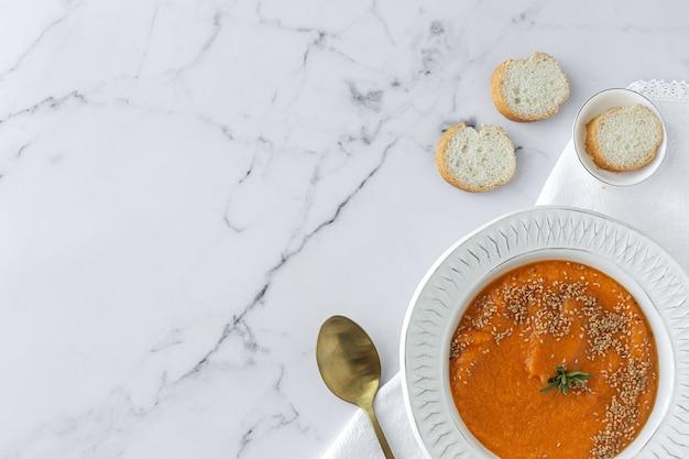 大理石のテーブルの上からパンと自家製の健康的なカボチャクリーム。フラットレイ
