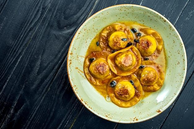 Домашние аппетитные равиоли с утиной грудкой и клюквой, подаются с соусом в синей тарелке на поверхности из темного дерева. блюдо итальянской кухни