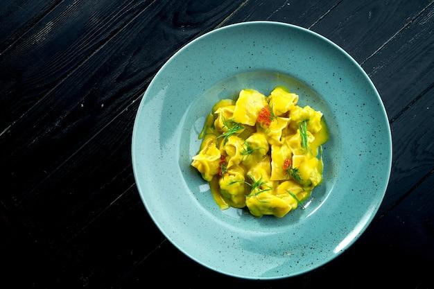Домашние аппетитные равиоли с лососем и икрой, подаются с заварным соусом в синей тарелке на поверхности из темного дерева. блюдо итальянской кухни