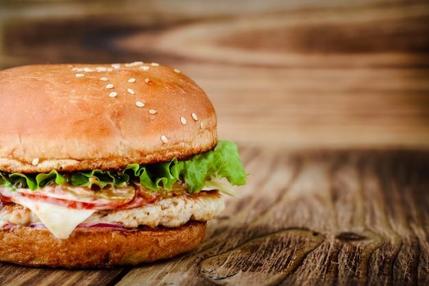 木製の背景に自家製の食欲をそそるチキンバーガー