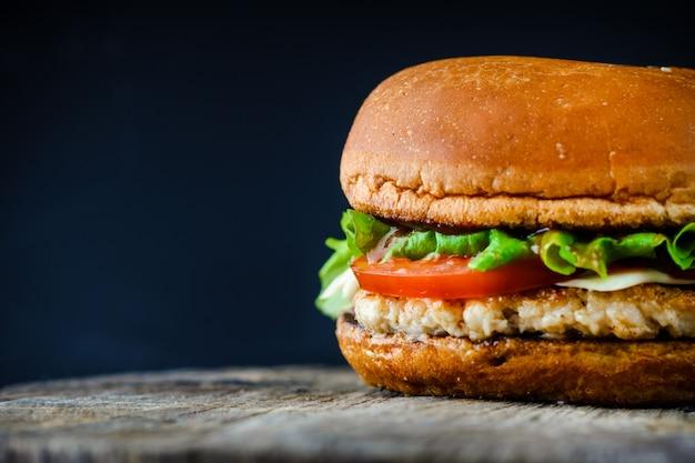 コピースペースと暗い背景に自家製の食欲をそそるチキンバーガー