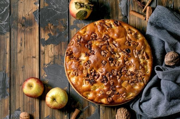 Самодельный пирог с яблоками и грецкими орехами шарлотта на тарелке со свежими садовыми яблоками, корицей и орехами вокруг на фоне темной деревянной доски. осенняя домашняя выпечка. плоская планировка, копия пространства