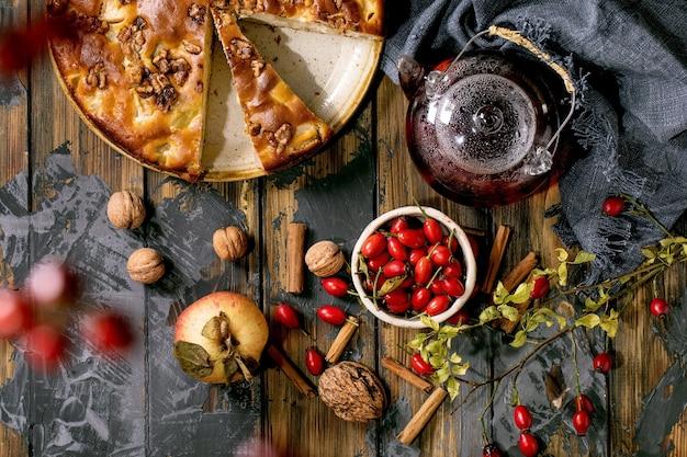 Самодельный яблочный и грецкий ореховый пирог шарлотта на тарелке со свежими садовыми яблоками, орехами, чаем из шиповника вокруг на фоне темной деревянной доски. осенняя домашняя выпечка. плоская планировка