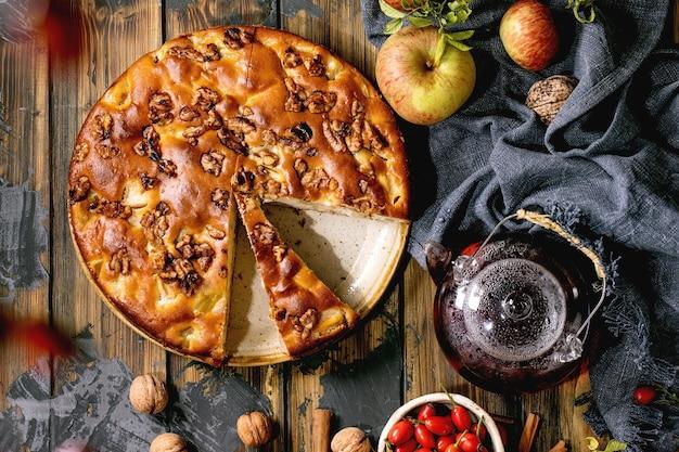 Самодельный яблочный и грецкий ореховый пирог шарлотта на тарелке со свежими садовыми яблоками, орехами, чаем из шиповника вокруг на фоне темной деревянной доски. осеннее чаепитие. вид сверху
