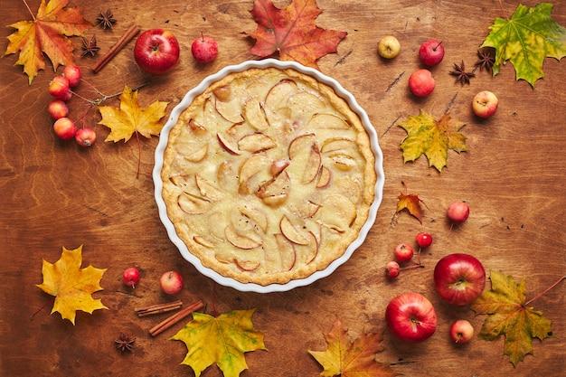나무 배경 위에 사워 크림 빨간 사과 크랩애플과 계피를 곁들인 홈메이드 사과 케이크...