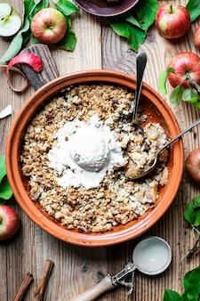 Gelato alla vaniglia con crumble di mele fatto in casa su un tavolo di legno