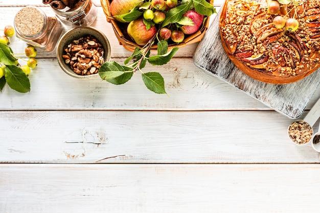 白い木製の背景に自家製アップルパイと食材。上面図。コピースペース