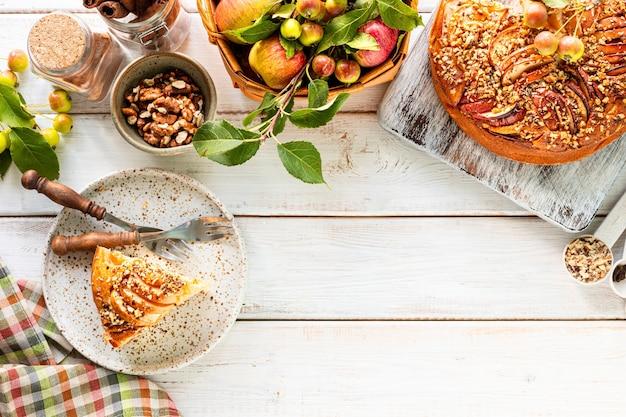 Домашний яблочный пирог и ингредиенты на белом фоне деревянных. вид сверху. копировать пространство