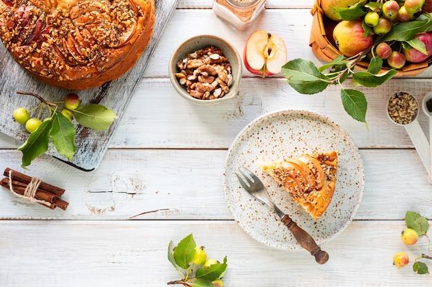 白い木製の背景に自家製アップルパイと食材。上面図。