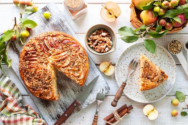 Домашний яблочный пирог и ингредиенты на белой деревянной поверхности