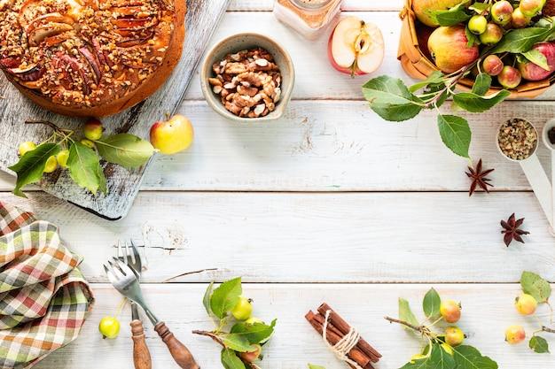 Домашний яблочный пирог и ингредиенты на белом деревянном. вид сверху. копировать пространство