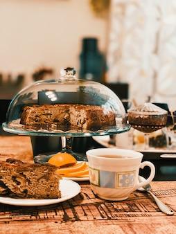 ガラスのスタンドにある自家製アップルパイは、お茶、レモン、スプーン、カットケーキです。
