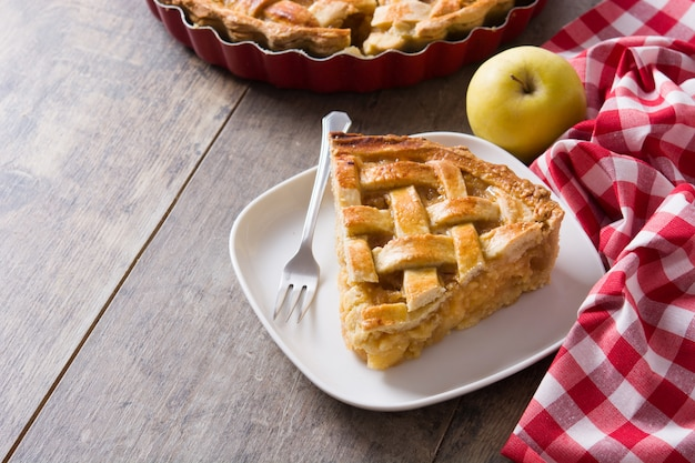 Homemade apple pie slice isolated on wood table copy space