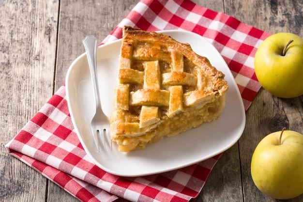 Homemade apple pie slice isolated on wood table