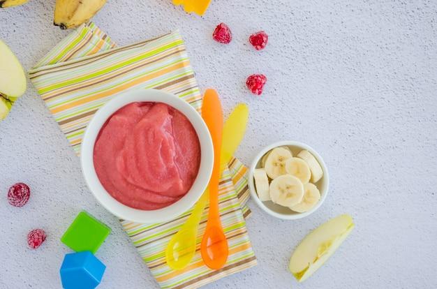 Домашнее яблочное пюре или соус с бананом и малиной в миске