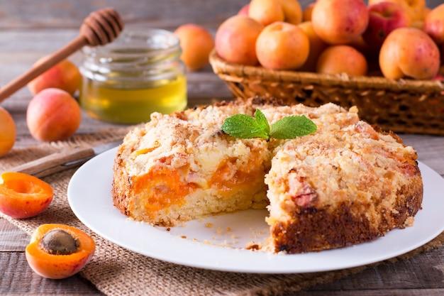 素朴な木製のテーブルに新鮮な果物と自家製アプリコットパイ