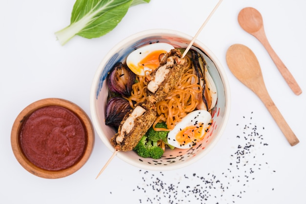 Домашняя азиатская японская еда с соусом; деревянная ложка и семена кунжута на белом фоне