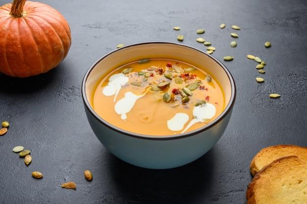 Домашний осенний крем-суп из тыквы со сливками, гренками, семенами и базиликом на темном деревянном фоне.