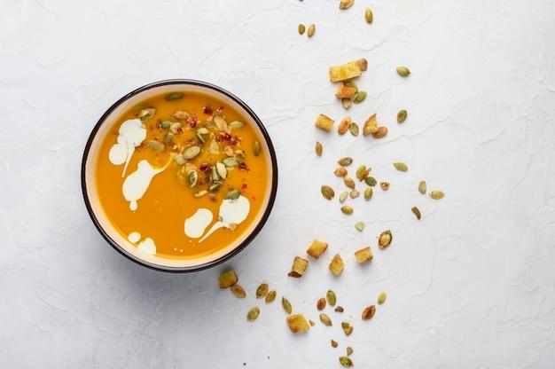 Домашний осенний крем-суп из тыквы со сливками, гренками, семенами и базиликом на светлом деревянном фоне.