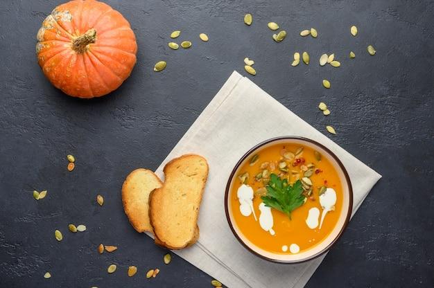 Домашний осенний крем-суп из тыквы со сливками, гренками, семенами и базиликом на льняной салфетке на светлом деревянном фоне.