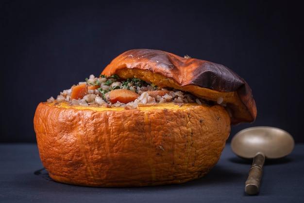 そば、にんじん、玉ねぎ、にんにく、プルーンを添えた自家製の秋のカボチャのぬいぐるみをクローズアップ。黒のスレートを背景に野菜とおいしい秋の焼きカボチャ