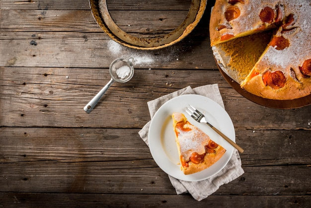 Homemade autumn and summer baked pastries. sponge cake with apricots. cut into pieces, plate, fork. on the stand. on the old wooden rustic table. copy space top view