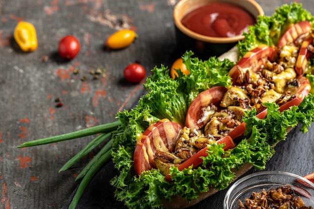 Домашние хот-доги с луком в беконе. жареное мясо, помидоры, листья салата и сырный соус. баннер, меню, место рецепта для текста, вид сверху.
