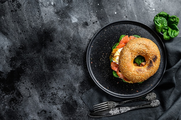 Homemade bagel sandwich with salmon, cream cheese, spinach and egg. black background