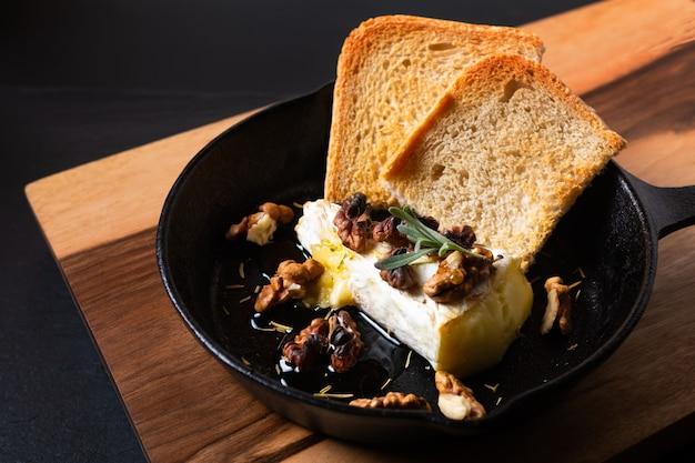 프라이팬 철 팬에 꿀과 호두를 곁들인 수제 구운 브리 치즈
