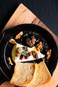 프라이팬 철 팬에 꿀과 호두를 곁들인 수제 구운 브리 치즈 프리미엄 사진