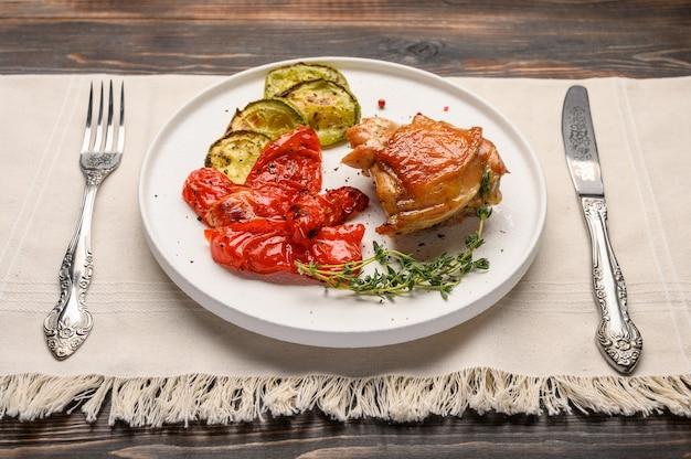 수제 구운 닭 허벅지, 호박, 간장, 향신료와 허브와 함께 린넨 냅킨에 흰색 접시에 칼과 포크와 고추