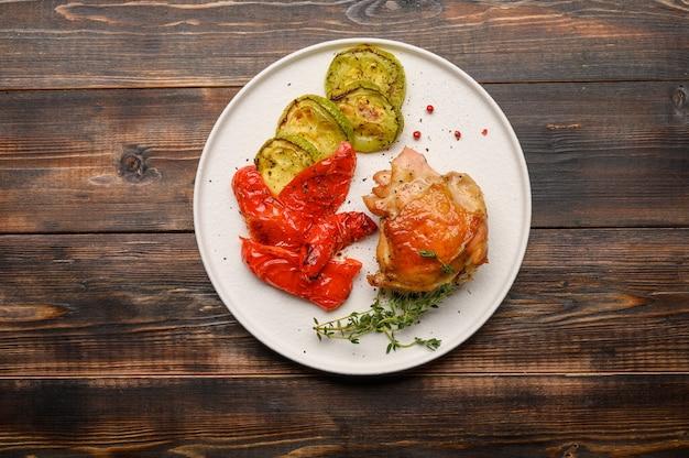 나무 표면에 하얀 접시에 간장, 향신료와 허브와 함께 집에서 구운 닭 허벅지, 호박, 고추