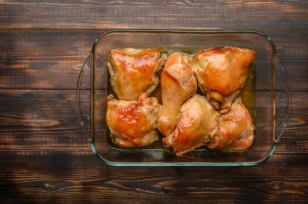 Домашние запеченные куриные бедра с соевым соусом и специями на стеклянном подносе