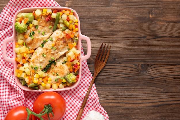 ダークウッドの背景にさまざまな調味料と野菜を使った自家製焼きチキン。
