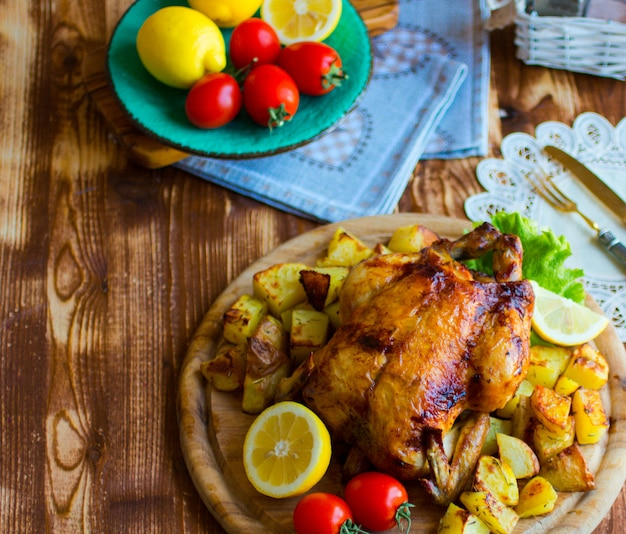 Homemade baked chicken with lemon and potatoes on a wooden background