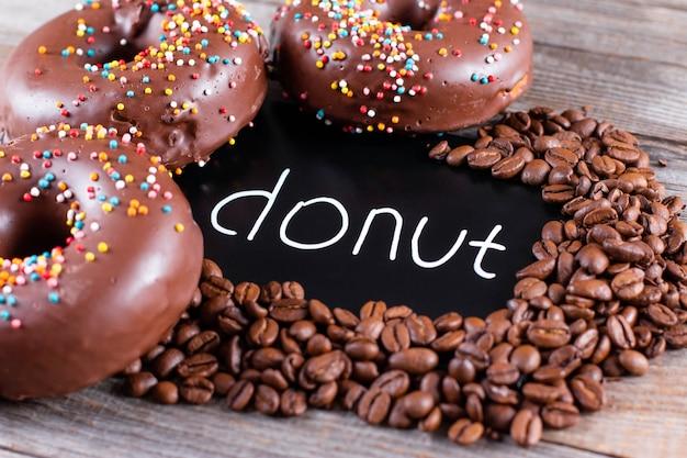 나무 테이블에 유약과 뿌리로 만든 구운 초콜릿 도넛