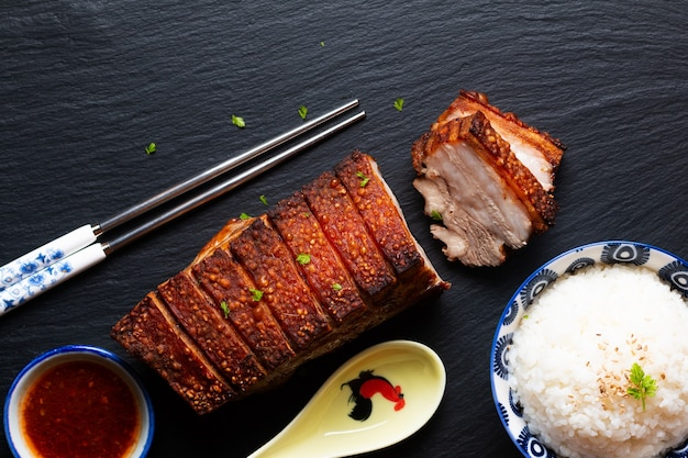 Homemade baked crispy pork belly on black slate stone board