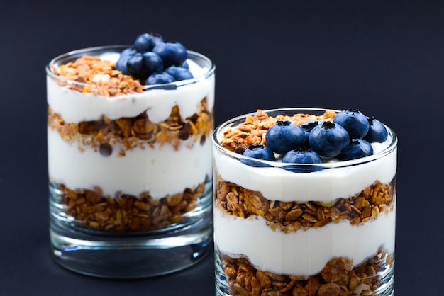 Homemade baked granola with yogurt and blueberries in a glass on a black background.