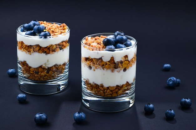 Homemade baked granola with yogurt and blueberries in a glass on black