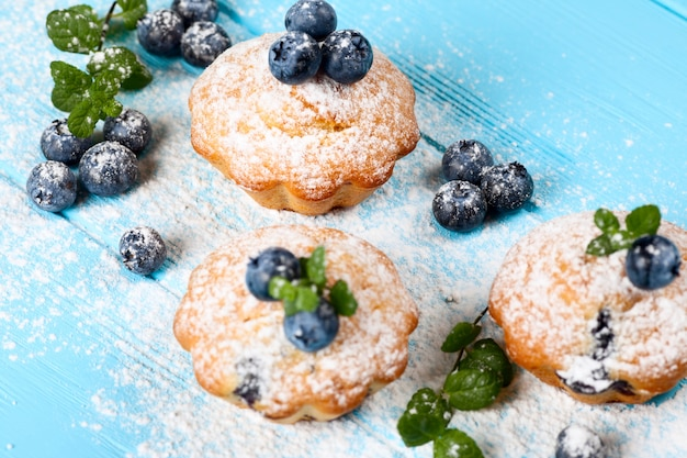 Homemade baked muffin with blueberries, fresh berries, mint, powdered sugar on blue wooden background.