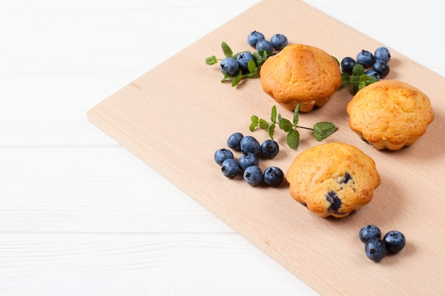 Homemade baked muffin with blueberries, fresh berries, mint on wooden background.