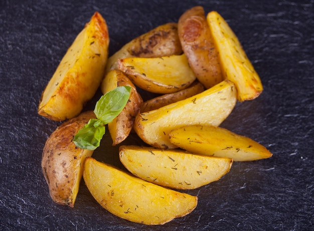 Homemade baked potato wedges with herbs on black background