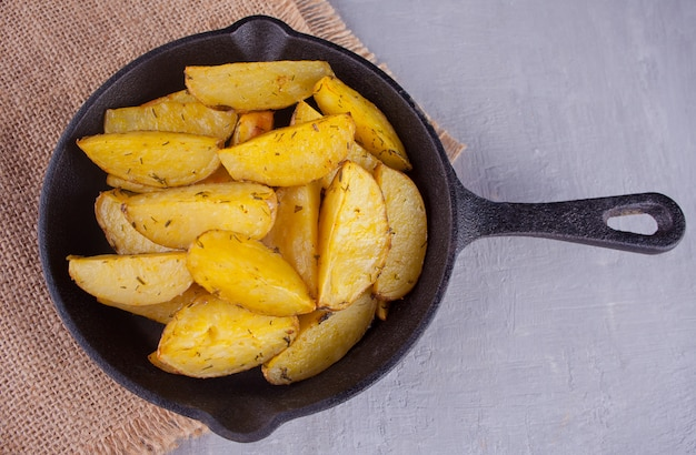 Homemade baked potato wedges with herbs on black iron pan on the gray background.